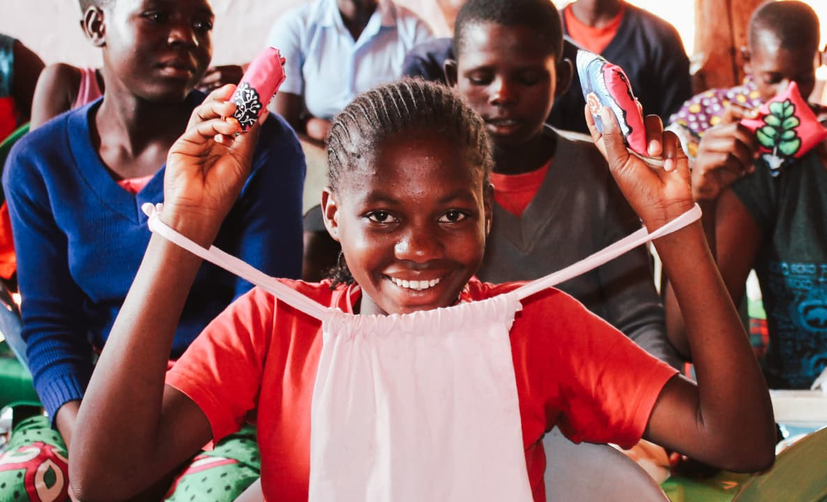 Young smiling girl holding up reusable sanitary pads